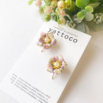 リバティ生地を使ったハンドメイドの花モチーフのピアス&イヤリングです。ホワイトベースに優しいパープルやピンクの花柄が優しい印象で、耳元に小さな春を咲かせます。
