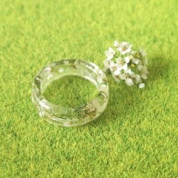 白い小さなドライフラワーを閉じ込めた透明感のある指輪。ラメも少し入っているので、光が当たると煌めきます。チェーンを通せばネックレスとして使うことも可能です◎