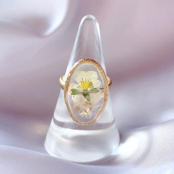 ゴールドのフレームの中にレジンで春のお花を閉じ込めた指輪。どこかアンティークのような雰囲気があり、手元をおしゃれに演出してくれます。
