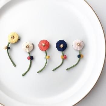 丸いお花とナチュラルなカーブが印象的な刺繍ブローチです。胸元にちょこんとつけたり、角度を変えたり、2色購入して組み合わせるのも素敵です。