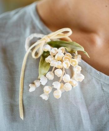 ほんのり光沢のある素材を使用したすずらんのブローチです。鈴なりに咲く姿が見事に表現されています。胸元にナチュラルな華やかさを添えてくれそうです。