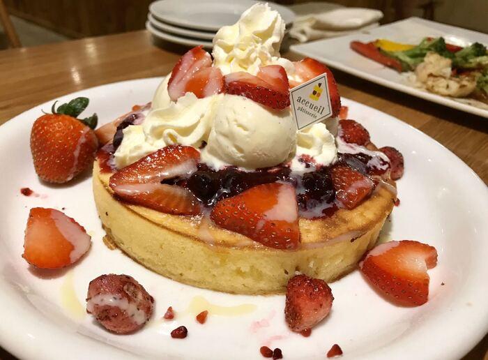 """まるでホールケーキのようなパンケーキは『アクイーユ』の「いちごベリーパンケーキ」。パティシエの作るパンケーキと言うことで、その""""映え""""るビジュアルも評判です。もっちりした生地は食べ応えもじゅうぶん。"""