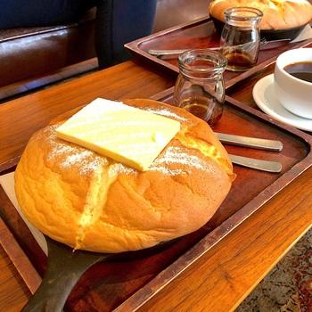 スキレットからはみ出すくらいのふっかふかのパンケーキは、『コンマ コーヒー』の「カステラパンケーキ」。上には無塩バターと粉糖がのっています。熱々のパンケーキにメイプルシロップをかけて、「じゅわ~」っと音まで楽しんで。