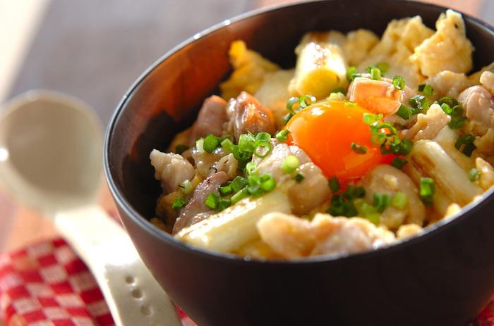 鶏もも肉、卵、白ネギで作る親子丼。焦げ目がつくまで焼いた白ネギが入った、香ばしくて美味な親子丼。中央にのせた卵黄との彩りもよく、食欲をそそります。