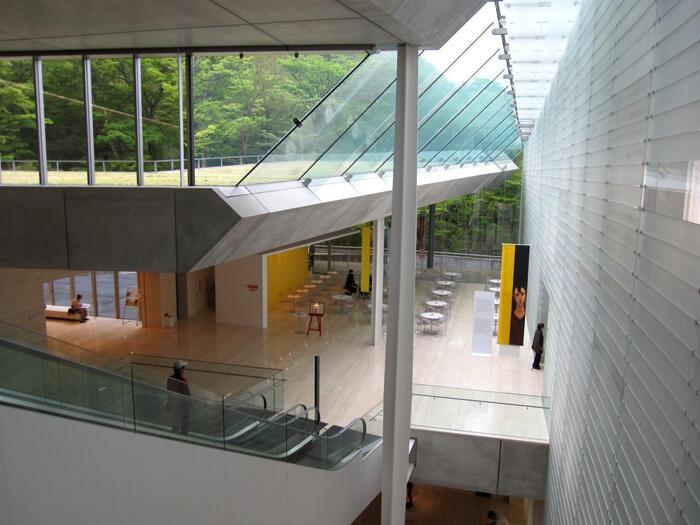日本建築学会賞など多くの建築賞を受賞した美しい建物も見どころのひとつ。山を借景にすることを計算して設計されており、自然の景観を損なわないように周囲を掘って造られています。ガラス張りの天井から自然光を受け、その季節にしか見られない景色を楽しみながらエスカレーターで降りて展示室へと向かう仕組みで、その風景がまるでアート作品の一部のよう。  また、建物の周りには様々な彫刻が点在した森の遊歩道があり、ブナやヒメシャラが群生する富士箱根伊豆国立公園内の自然を感じて、心地よいひとときを過ごすことができます。