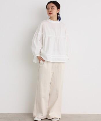 白のワイドチノパンに、白のブラウスを合わせた着こなし。襟元のフリルデザインで大人ガーリーな雰囲気をアピールしつつ、足元はスニーカーでカジュアルにまとめています。デイリーコーデにもぴったりなスタイリングですね。