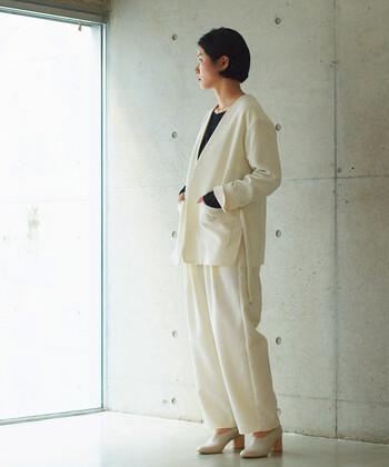 白のタック入りワイドパンツに、深めVネックの白トップスを合わせたコーディネートです。インナーは黒の長袖で、しっかりと色を覗かせたモノトーンコーデに仕上げています。足元も白系のヒールシューズで、ナチュラル×フェミニンな着こなしに。