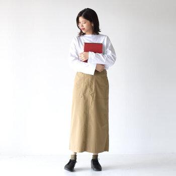 白のボートネックロンTに、ベージュのタイトスカートを合わせたコーディネート。黒シューズにカーキカラーの靴下を合わせて、シンプルアイテムにほどよいワンアクセントをプラスしています。どんなアウターや羽織もOKの万能コーディネートです。