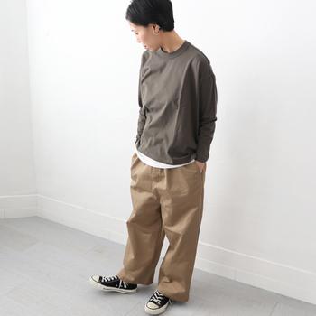 ブラウン系のシンプルなロンTに、ベージュのワイドパンツを合わせたカジュアルなコーディネート。インナーの白トップスを裾からチラ見せして、程よいワンアクセントを加えています。足元も白黒のベーシックなスニーカーで、デイリーに使えるアクティブな着こなしに。