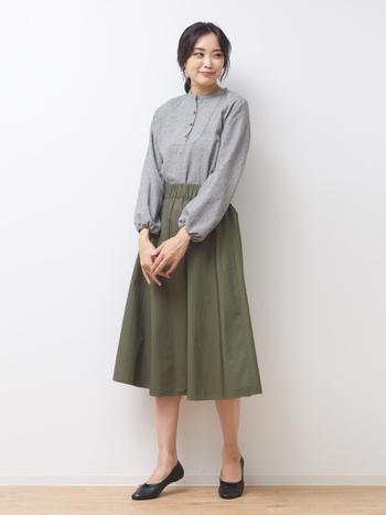 カーキカラーのミモレ丈スカートに、グレーのブラウスをきっちりとタックインしたコーディネートです。足元は黒のパンプスで上品な雰囲気にまとめて、オフィスカジュアルにも使える大人の着こなしに仕上げています。