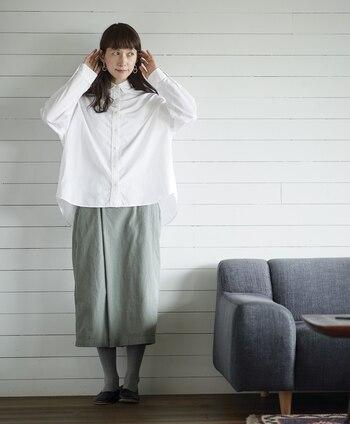 タイトシルエットのカーキスカートに、白のワイドシャツを合わせたコーディネート。シャツはタックインせずにあえて裾を出すことで、きちんとしすぎずデイリーに使える着こなしに仕上げています。グレーのタイツと黒のフラットシューズで、落ち着いた雰囲気に。