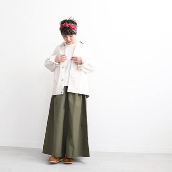 ロング丈のカーキカラースカートに、白トップスと白のデニムジャケットを合わせた着こなしです。頭に巻いた赤のバンダナが、白とグリーンに程よいアクセントカラーをプラスしてくれます。ボーイッシュながらも爽やかなカラーリングで、大人のカジュアルコーデにぴったりなスタイリングに♪