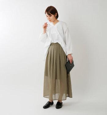 透け感がトレンド感たっぷりなカーキカラーのスカートに、白のブラウスをフロントだけタックインしたスタイリングです。サイドを出してゆるく着こなすことで、大人のこなれ感を演出しています。小物は黒で揃えて、引き締めカラーとして活用しているのがポイント。