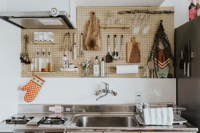 ディアウォールに有孔ボードを貼って、キッチンの壁面収納に。フックを引っかけてキッチンツールを吊るしたり、トレーなどを取り付けて、洗剤や調味料を置いています。流木やドライフラワーをさり気なく飾った、センスが光る見せる収納です。