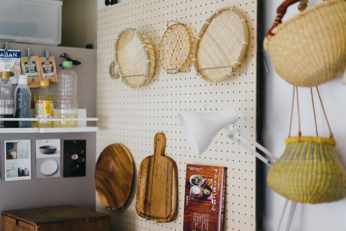 つっぱり棒と有孔ボードを使った壁面収納です。かごやカッティングボード、レシピ本を飾って見せる収納に。ゆとりをもって配置することで、雑然とせずにすっきり見せることができますね。
