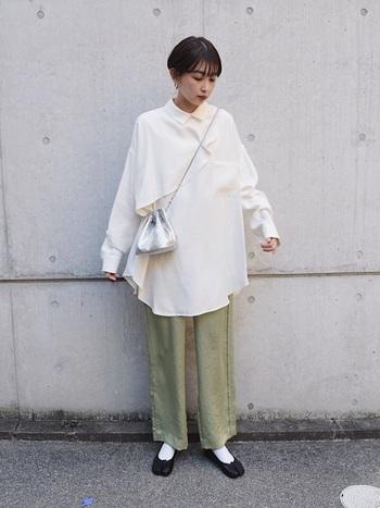 ペールグリーンの細身ストレートパンツにオーバーサイズのデザインシャツを合わせた上級者コーデ。シルバーの巾着バッグが程よいアクセントになっているのも◎
