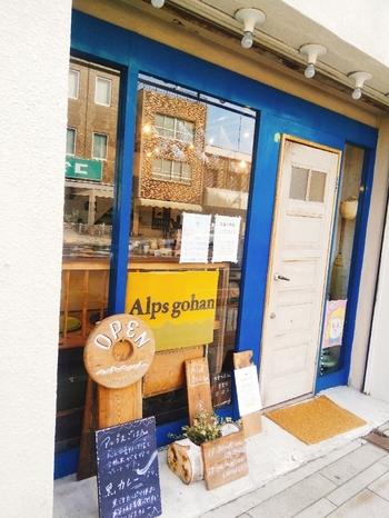 ブルーの外壁に白いドア、黄色の看板が可愛いお店。中はL字カウンターのみ8席。産地も農法もさまざまなこだわりの野菜を、素敵な一皿に仕上げてくれます。旬の野菜や新しい食材のことなど、興味深いお話も聞けますよ。