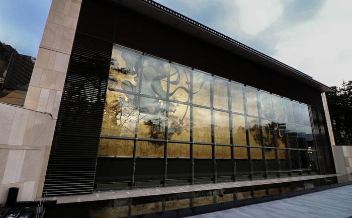 琳派や伊藤若冲などの近世・近代の日本の有名な絵画と、数千年の歴史を辿れる中国陶磁を始めとした陶磁器を中心として、5階建ての広い会場に数多くの美術品を収蔵する岡田美術館。  敷地内に入ってまず目を惹くのは、美術館壁面の「風神雷神図屏風」を再現した大壁画「風・刻(かぜ・とき)」。雄大な山に囲まれた箱根という立地をイメージして、左の風神の衣はより大胆にはためくなど、作家のオリジナリティが盛り込まれ、迫力満点です。