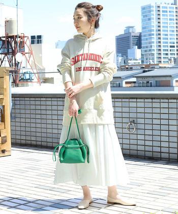 白いエスカルゴスカートは、ふんわりとした形がエアリーで素敵。あえてパーカーを合わせてカジュアルダウンしたら、大人の休日コーデに。鮮やかなグリーンのバッグを差し色に取り入れて。
