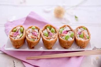 梅酢や干し桜海老を使って彩りよく炊き上げたおこわを、枝豆とともに味付けした油揚げに詰めます。最後に桜の花を彩りにのせて。花見弁当にもぴったりの春爛漫のいなり寿司です。