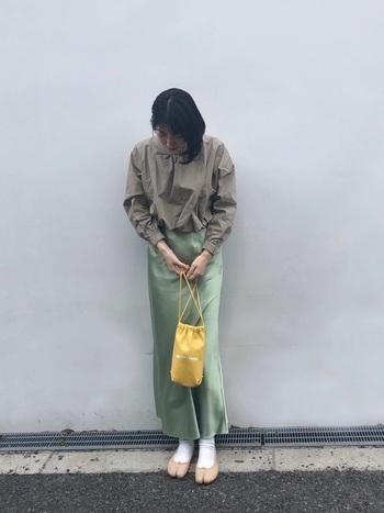 深みのあるグリーンのサテンスカートはすらりとした女性らしいラインを表してくれます。きちんと感のあるトップスをウエストインして、よそ行き感をアップしています。