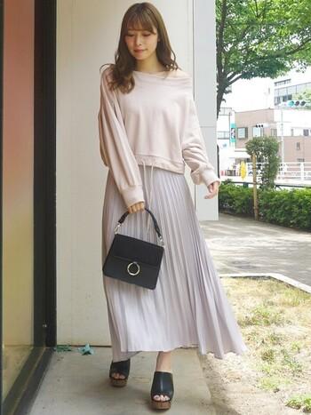 見る角度によって色味が変わって見えるシャイニーサテンのプリーツスカートです。裾のあたりでプリーツが淡く消え、洒落た雰囲気を演出できます。