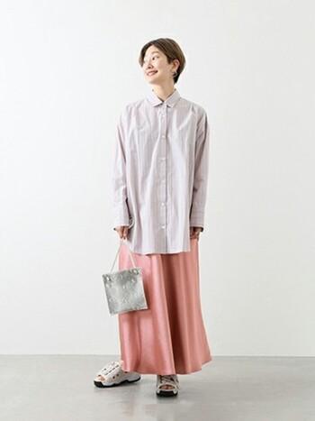 明るいピンクのサテンスカートは、春の訪れを感じさせてくれるもの。ほどよい光沢感で、さりげなく上品さをアレンジしています。