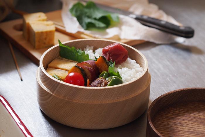 このように白木の器はご飯を美味しく見せてくれるので、お弁当を食べるだけではなく作る楽しみも感じさせてくれます。お弁当の蓋はちょっとしたプレート代わりになるので、飲み物を乗せるコースターとして使ったりと実用性もあります。なによりもこのシンプルなフォルムと美しい木目が魅力的なお弁当箱です。