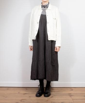 デニムのサロペットワンピースに、ボーダーのハイネックと白のデニムジャケットを合わせたスタイリング。足元はダークトーンでまとめて、ジャケットの白を主役にしたコーディネートです。