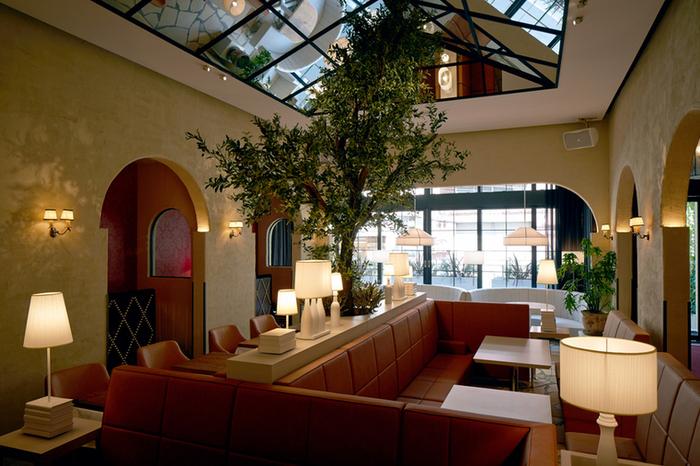 店内は全席ソファのゆったりできる雰囲気。シンボルのように枝を広げるグリーンの木や、開放感を演出する鏡張りの天井が目を引きます。壁際の奥まった場所には半個室のカップルシートもあるので、ゆったりデートを楽しめますよ。