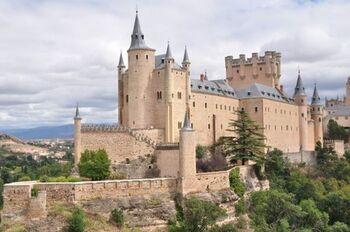 『白雪姫』の城のモデルになったと言われているのが、スペインのアルカサル城。マドリードからバスで1時間強の位置にある世界遺産都市セゴビアの山頂に建っています。側面の姿は優美、そして正面は趣が異なり厳かな風格を備えています。
