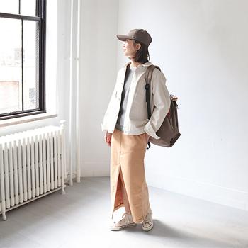 グレートップスに、ベージュ系のタイトスカートを合わせたシンプルアイテム同士のスタイリング。白のデニムジャケットをプラスして、おしゃれ度をアップしています。リュック・キャップ・スニーカーのカジュアル小物で、白のデニムジャケットを上手に着こなしていますね。
