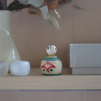 宮城県・鳴子温泉に伝わる「鳴子こけし」は、面長で瓜実顔(うりざねがお)という特徴があります。また、首を回すと心地よい音がします。  江戸時代の後期から歴史は始まり、子どもの成長を願う「縁起物」として親しまれています。頭部の水引手と胴の菊模様がお祝いごとの象徴とされています。