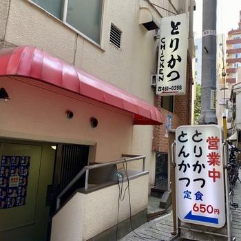 路地裏にひっそりと佇む、渋谷の老舗定食屋「とりかつチキン」。営業中の看板が目印です。