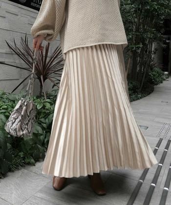 ゴールドのプリーツサテンスカートは、コーディネートをぱっと華やかに仕上げてくれます。同じベージュ系のやわらかなニットとあわせると、異素材を遊ぶおしゃれ上級者に。大人らしいコーデになりますね。