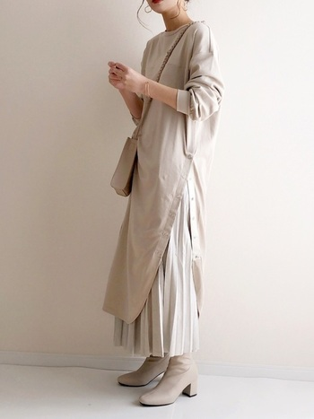 ロング丈のカットソーワンピースにプリーツスカートをレイヤードした同系色コーデ。デザイン性あるワンピからのぞくプリーツの裾がおしゃれです。バッグやブーツもグレージュで合わせて、こなれ感のある着こなしに。