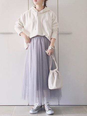 オフホワイトのオーバーサイズパーカーにモーブのチュールスカートの組み合わせ。パーカーの一部をフロントインすることですっきり。バッグや靴下など細かい所までオフホワイトで統一した洗練されたスタイルです。