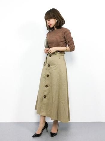 ブラウンのプチハイネックニットとトレンチ風スカートのトラッドなきれいめスタイリング。首元まであるすっきりニットと、張りのある生地のスカートは、春らしい装いながら、朝晩の冷えや肌寒い日にも大活躍する、優秀アイテムです。