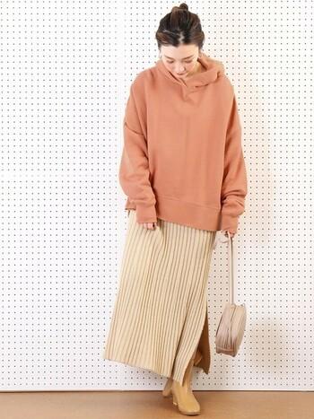 着ているだけで気分高まるオレンジカラーのゆったりパーカー。上品なニットスカートやヒールブーツを合わせることでフェミニンな仕上がりに。オレンジ×ベージュの統一感のある配色も◎