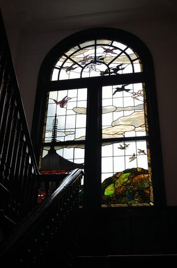"""ここ「鳩山会館」は、いわば、小川三知作品の宝庫。 それほどまでに、小川の制作したステンドグラスが状態が良いままに数多く残り、今も色鮮やかに光を透過し続けています。  階段踊り場の一番大きな『五重塔と鳩』の他、応接室やサンルーム、玄関ホールにも、鳩山家のシンボルマーク""""鳩""""などをモチーフとした作品が嵌め込まれています。"""