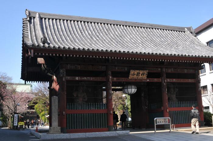 ここ「護国寺」は、東京の中で屈指の寺格を誇る名刹の一つです。  江戸幕府・第五代将軍綱吉の生母・桂昌院(けいしょういん)の発願によって、天和元(1681)年に創建された真言宗豊山派の大本山。桂昌院が帰依していた「大聖護国寺(群馬県高崎市)」から亮賢僧正が招かれ開山した寺院です。  【有楽町線・護国寺駅、護国寺方面出口から地上に出たすぐの所に建つ護国寺の「仁王門」。 壮麗な丹塗の門は、元禄10(1697)年建立。伽藍の中でも重要な表門となっている。南側の正面右に阿形(あぎょう)像、左に吽形(うんぎょう)像の二体の仏像、その北側の背面には、増長天と広目天の二天像が安置されている。】