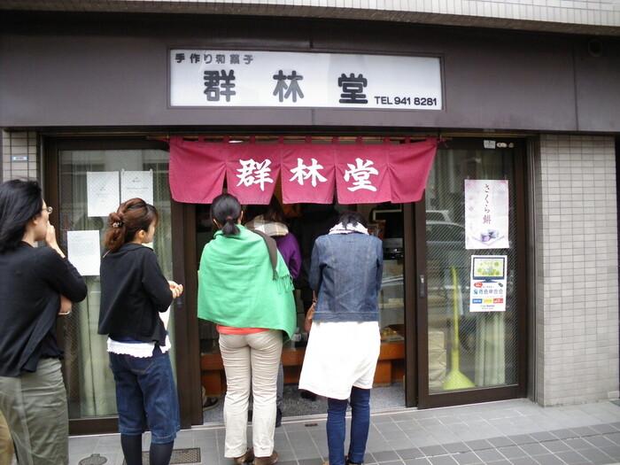 """護国寺駅から徒歩1分程の「群林堂」は、遠目でも分かる程に行列が目印。 近隣のみならず、遥か遠方からその味を楽しみに訪れる人が多く、行列が見えなかったら、店が定休日か、""""豆大福""""が売り切れかのどちらか。それ程までに""""豆大福""""で人気を博している和菓子店です。"""