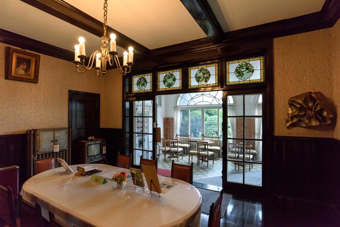 鳩山邸は、地上2階、地下1階の鉄筋コンクリート造。人造石や煉瓦タイルで装飾された壁面、アーチや矩形のバランス良く配置させた開口部、鹿の頭や鳩といった外部装飾等など、特徴ある建築様式や遊び心を随所に取り入れ、柔らかで穏やか、瀟洒な雰囲気を演出しています。【1階食堂とサンルーム】