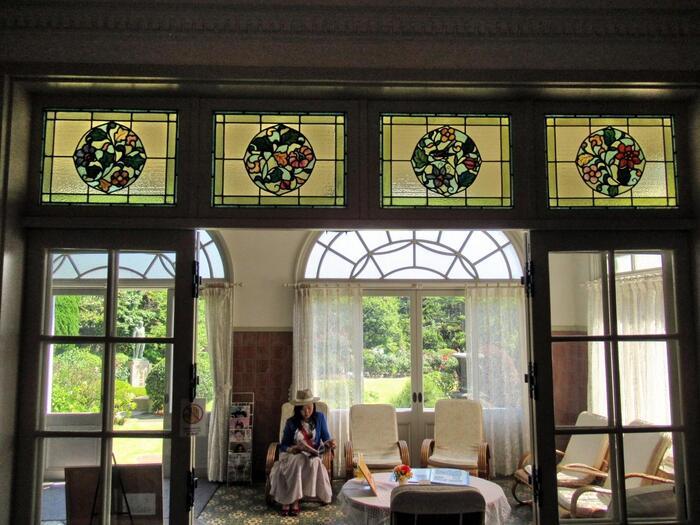 外部と内部の繋がりも良く、室内と庭園の間には、外光が良く入る「サンルーム」が設置され、当屋敷を特徴づけています。「サンルーム」では、見学者も当時そのままの気分で休憩出来ます。 【小川三知作のステンドグラスが嵌め込まれた「サンルーム」の仕切りガラス戸。】