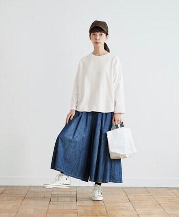 一見するとスカートにも見えるキュロットパンツ。真っ白で無駄のないシンプルなトップスに加え、シューズやバッグも白で合わせているので、濃紺デニムのボトムスでも明るい装いに仕上がっています。気取らないシンプルさが素敵です。