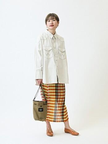ワイルドなメンズシャツというイメージが強いデニムのタンガリーシャツですが、可愛らしいチェックのタイトスカートと合わせるとこんなに女性らしいコーデに!フラットなパンプスも、上下のバランスを保つカギになっているのでお手本にしたい着こなしです。