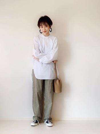 ホワイトのシャツを大人カジュアルに仕上げるなら、細かいチェック柄パンツと黒スニーカーを合わせて。大ぶりのピアスでこなれ感もプラス。