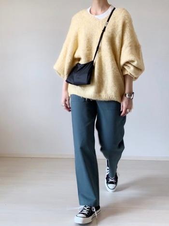 優し気イエローのニットに、ゆったりパンツを合わせて。スニーカーとバッグを黒で統一すれば、まとまり感もアップ。