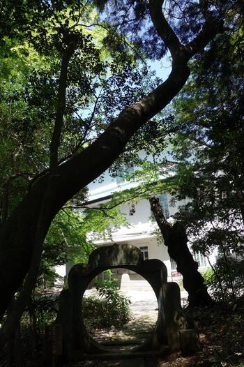 当地は、後述する「肥後細川庭園」と併せて、幕末から戦後にかけて細川家の屋敷があった場所で、「永青文庫」は、その広大な敷地の一角に位置しています。胸突坂の入口が正門ですが、細川庭園と地続きですので、庭園側からも入ることが出来ます。  【「永青文庫」と「肥後細川庭園」を繋ぐ通路上にあるアーチ状の石のオブジェ】