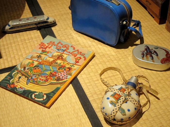 畳の上にはアルミ(アルマイト)のお弁当箱や水筒が。戦前から普及しつつあったアルミのお弁当箱には、人気のアニメのキャラクターや、ロケットなど子供達が憧れるような絵柄が施されました。